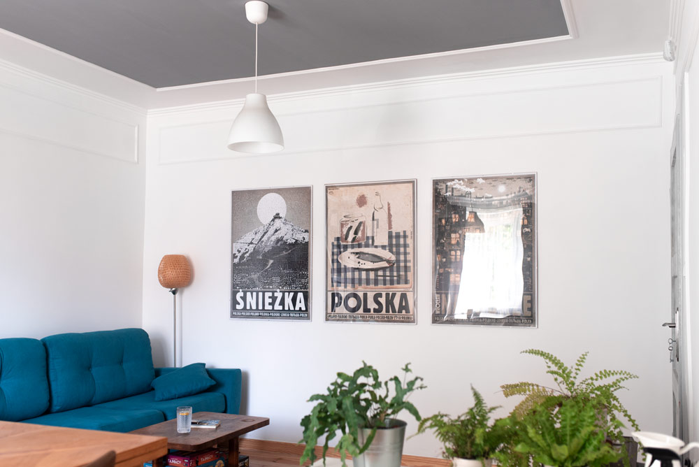 metamorfoza projekt salonu po polsku - z plakatami Ryszarda Kai, paprotkami i szarym sufitem